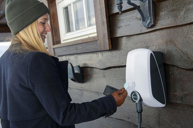 Frau mit RFID Karte an EVBox Ladestation für E-Auto