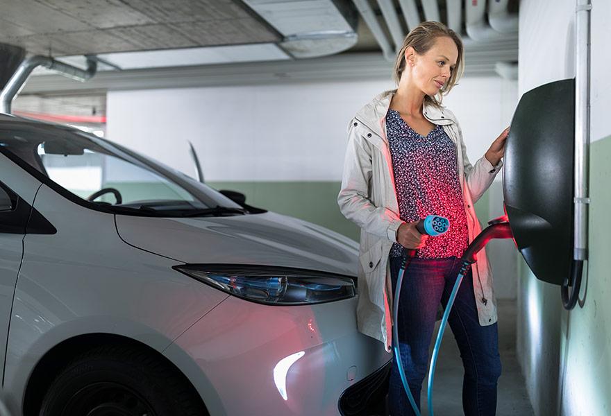 Frau lädt an Wallbox für Elektroautos im Mietshaus