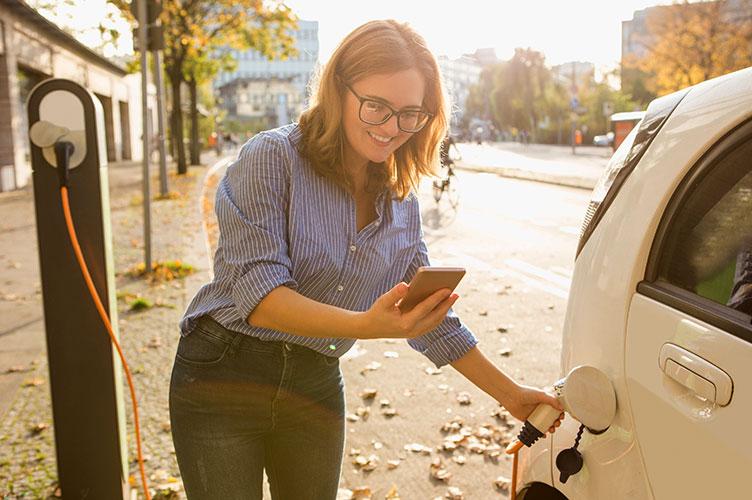 Frau lädt Auto an öffentlicher Ladestation